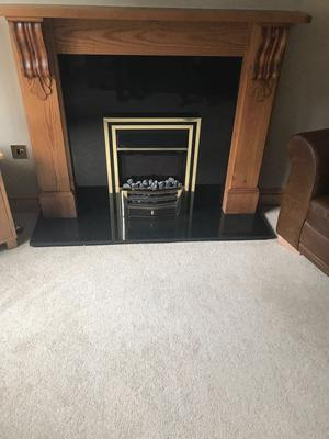 electric coal effect fire, wooden surround and black granite effect plinth.