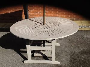 Solid wood circular patio table and 6 solid wood arm chairs. Also include matching parasol and base